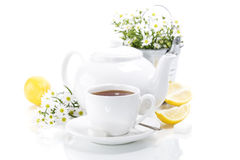 Tea with lemon. A cup of tea with lemon and flowers over white Royalty Free Stock Photography