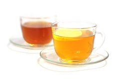 Tea with a lemon. Tea is poured in two cups, tea with a lemon, is isolated on white Stock Photo