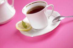 Tea with lemon. Tea and white cup on the pink background Stock Photography