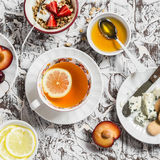Tea with lemon, blue cheese, biscuits, honey, yogurt with granola and fruit on a light background. Stock Photo