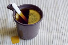 Tea with lemon is brewed in a plastic Cup. In a disposable glass of tea bag and spoon royalty free stock image