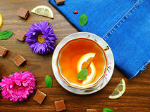 Tea with lemon. Composition made of teacup,chocolate and fresh flowers stock photos