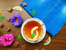 Tea with lemon. Composition made of teacup,chocolate and fresh flowers royalty free stock photo