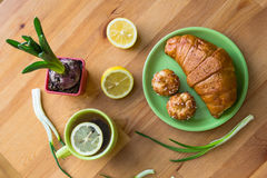 Tea with lemon and croissant for fresh spring breakfast Stock Images