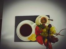 Tea lemon cup mug white plate coffee. Fruits strawberry grapes whitegrapes blackplate blackbackground Royalty Free Stock Photo