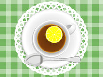 Tea with lemon. Cup of tea with lemon on a napkin and green tablecloths Stock Photo
