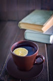 Tea with lemon. In cup and old books Stock Image