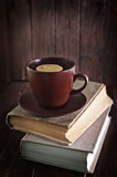 Tea with lemon. In cup and old books Stock Images