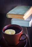 Tea with lemon. In cup and old books Royalty Free Stock Photography