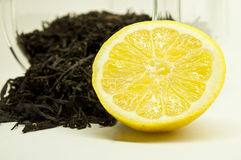 Tea with lemon. Dry tea leaves and vivid yellow lemon fruit Royalty Free Stock Photos
