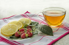 Tea with lemon and fresh  raspberry. Are on table Royalty Free Stock Image