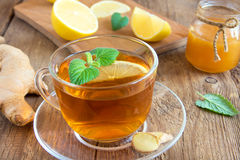 Tea with lemon, ginger, honey and mint. Leaves in transparent cup over rustic wooden background Royalty Free Stock Photography