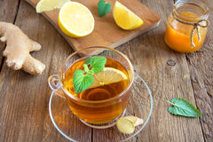 Tea with lemon, ginger, honey and mint. Leaves in transparent cup over rustic wooden background Royalty Free Stock Image