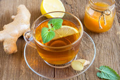 Tea with lemon, ginger, honey and mint. Leaves in transparent cup over rustic wooden background Stock Images