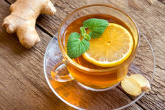 Tea with lemon, ginger and mint. Leaves in transparent cup over rustic wooden background Royalty Free Stock Photography