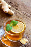 Tea with lemon, ginger and mint. Leaves in transparent cup over rustic wooden background Stock Images