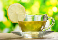 Tea with lemon on green leaves Stock Photography