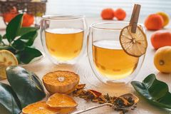 Tea with lemon, mandarins, dry fruits and citrus leaves on a kitchen table royalty free stock photo