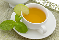 Tea with a lemon and mint. White cup with a branch of mint and limes Stock Photography