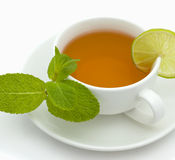 Tea with a lemon and mint. White cup with a branch of mint and ������ on a white background Royalty Free Stock Photos