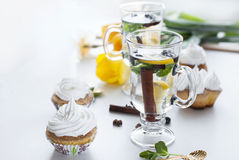 Tea with lemon and mint cupcakes with cream and yellow tulips Royalty Free Stock Images
