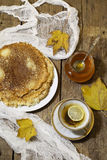 Tea with a lemon, pancakes, honey and autumn leaves Royalty Free Stock Photography