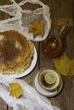 Tea with a lemon, pancakes, honey and autumn leaves Stock Photos