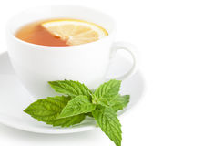 Tea with lemon. Tea with piece of lemon and mint on a plate over white background Stock Photography