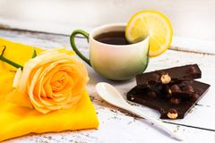 Tea with lemon, rose and black chocolate royalty free stock image