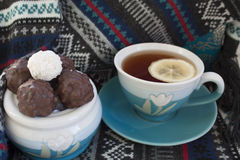 Tea with lemon and sweets. Cup of black tea with lemon and chocolate, scarf Royalty Free Stock Photo