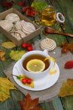 Tea with lemon on a table strewn with autumn foliage. Tea, marshmallows and a jar of honey on a wooden table. Autumn still life Royalty Free Stock Image