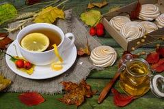 Tea with lemon on a table strewn with autumn foliage. Tea, marshmallows and a jar of honey on a wooden table. Autumn still life Stock Photos