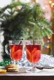 Tea with lemon, tangerines, cookies and nuts in Christmas decor with Christmas tree, nuts and apples on colorful background bokeh Stock Photo