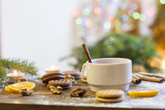 Tea with lemon, tangerines, cookies and nuts in Christmas decor with Christmas tree, nuts and apples on colorful background bokeh Royalty Free Stock Photography