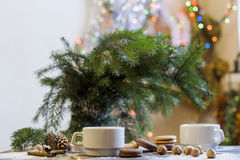 Tea with lemon, tangerines, cookies and nuts in Christmas decor with Christmas tree, nuts and apples on colorful background bokeh Stock Photography