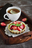 Tea with lemon tartlet with cream and strawberries in a vintage tray Royalty Free Stock Photo