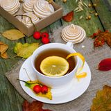 Tea with lemon. On a wooden table. Table strewn with autumn leaves Royalty Free Stock Images