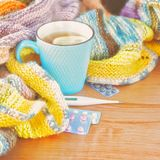 Tea with lemon, thermometer, pills and a knitted blanket. Royalty Free Stock Photography
