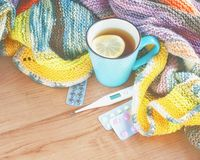 Tea with lemon, thermometer, pills and a knitted blanket. Royalty Free Stock Photo