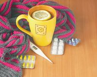Tea with lemon, thermometer, pills and a knitted blanket. Stock Photos