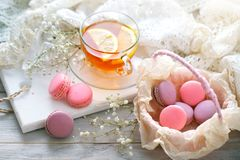 Tea with lemon, wild flowers and macaron on white wooden table. Delicate still life stock photography