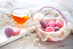 Tea with lemon, wild flowers and macaron on white wooden table. Delicate still life stock image