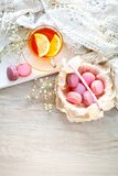 Tea with lemon, wild flowers and macaron on white wooden table. Delicate still life royalty free stock photos