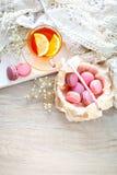 Tea with lemon, wild flowers and macaron on white wooden table. Royalty Free Stock Photos