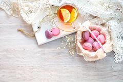 Tea with lemon, wild flowers and macaron on white wooden table. Delicate still life royalty free stock image