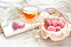 Tea with lemon, wild flowers and macaron on white wooden table. Delicate still life stock photo
