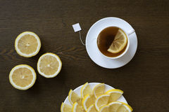Tea with lemon on wooden board. Slices of lemon on a plate Royalty Free Stock Photo