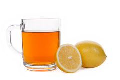 Tea and lemons. Red Ceylon tea in a glass cup and two lemons on a white background. Isolated Royalty Free Stock Photos