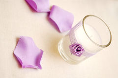 Tea light candle. A closeup of a candle in a glass holder decorated with a rose ribbon and lilac flower petals around it Royalty Free Stock Image