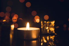 Tea Light Candle burning with bokeh lights on black background.  Royalty Free Stock Image